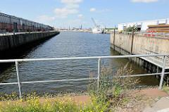 Blick vom Baakenkai in den Baakenhafen; ein Schiff liegt am Versmannkai - lks. der Petersenkai mit Lagerschuppen - im Hintergrund das Hamburg-Panorama mit den Kirchtürmen der Hansestadt.