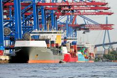 Containerfeeder im Hamburger Hafen am HHLA Containerterminal Burchardkai unter Containerbrücken - im Hintergrund die Köhlbrandbrücke.