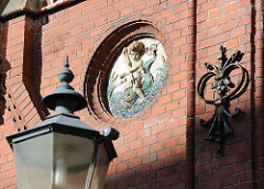 Gusseiserne Laterne und Dekorelement mit Maueranker an der Köhlbrandtreppe Altonas.