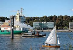+ 44 Schiffsverkehr auf der Elbe vor Hamburg Ottensen - ein Containerfeeder verlässt den Hambuger Hafen - Bürogebäude am Elbrand. Ein Segelschiff fährt elbaufwärts.