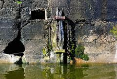 Verwitterter Holzpfahl mit langer Eisenkette im Hamburger Hafen - Kaimauer mit Moos bewachsen.