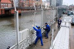 Abbau des Zollzauns am Zollkanal Kannengiesserbrücke in der Hamburger Speicherstadt- zwei Arbeiter nehmen den drei Meter hohen Maschendrahtzaun aus der Verankerung.