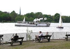 Parkbänke an der Aussenalster - der historische Alsterdampfer St. Georg fährt über die Alster.