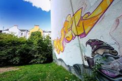 Graffiti an einer Hauswand - Wohnhäuser im Grünen.