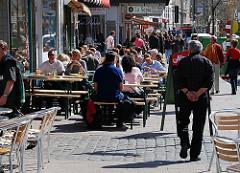 Restaurant mit Tischen in der Sonne auf der Strasse - Passanten auf dem Bürgersteig.