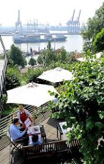 Blick von der Elbchaussee in Hamburg Othmarkschen auf die Elbe - ein Containerschiff verlässt den Hamburger Hafen - im Hintergrund die Hafenanlagen des Container Terminals Burchardkai.
