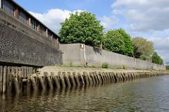 Streichdalben aus Holz schützen eine Kaimauer Rosskanal im Hamburger Hafen.