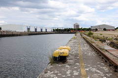 Petersenkai am Baakenhafen - Eisenpoller und Schiene für die Führung des Hafenkrans - Lagergebäude.