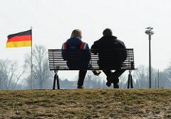 Paar auf einer Bank auf dem Elbdeich in Hamburg Kirchwerder - Deutschlandflagge im Wind.