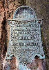 Gedenkstein am Platz der Republik in Hamburg Altona -  Bronzetafel an einem Findling; Inschrift: DIESEN SCHMUCKPLATZ VERDANKT DIE STADT ALTONA DER JUBILÄUMSGABE DES ALTONAISCHEN UNTERSTÜTZUNGS-INSTITUTS, 28. Januar 1899.