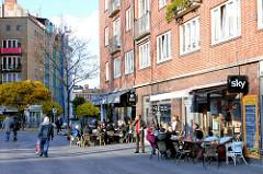 Herbstsonne in Hamburg St. Georg sitzen die Gäste im Cafe auf dem Gehweg am Hansaplatz.