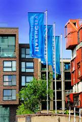 Flaggen der Hafencity wehen im Wind - moderne Hamburger Architektur im Hintergrund.