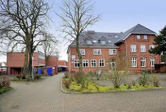 Altes Schulgebäude in Hamburg Hausbruch - erbaut 1896; Backsteinfassade - daneben Schulneubauten der 1960er Jahre.