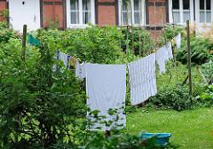 Wäsche trocknen auf der Leine im Garten - Fachwerkgebäude in Hamburg Sinstorf.
