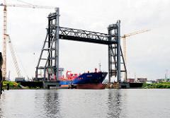 Die Rethehubbrücke wurde hochgefahren - ein Frachtschiff unterquert die historische Brücke im Hamburger Hafen und fährt in den Reiherstiegkanal ein.
