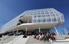 Besucher der Hafencity in der Sonne auf der Treppe vor dem Unilever- Verwaltungsgebäude.