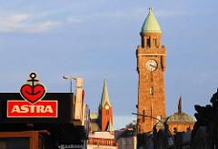 Abendsonne am Hamburger Hafen - Werbung für Astrabier und der Uhrenturm der Landungsbrücken.