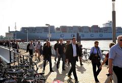 Fähranleger Teufelsbrück, eine Fähre aus Finkenwerder hat gerade angelegt. Auf der Elbe fährt ein Containerriese Richtung Hamburger Hafen.