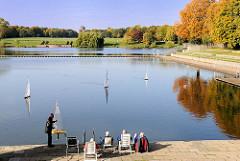 Stadtparksee Freibad - Modellbootbesitzer gehen ihrem Hobby nach und lassen die ferngesteuerten Segelschiffe auf dem Wasser fahren - im Hintergrund farbige Herbstbäume des Hamburger Stadtparks.