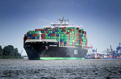 Das Frachtschiff HATSU COURAGE läuft mit Containern hoch beladen aus dem  Hamburger Hafen aus; das Frachtschiff  hat eine Länge von 334 m und kann 8073 Container TEU transportieren.