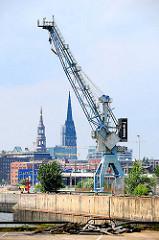 Hafenkran am Versmannkai - Kirchtürme der Hamburger St. Petrikirche und St. Nikolaikirche im Hintergrund.