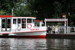 Alsterschiff Saselbek am Anleger Winterhuder Fährhaus, Fahrgäste erwarten die Ankunft des Schiffs.