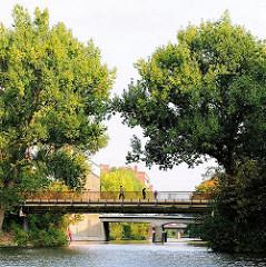 Brücke mit Fussgängern über den Mittelkanal - grosse Bäume stehen an der STrasse in Hamburg Hammerbrook.