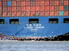 Heck des Containerschiffs HYUNDAI COURAGE beim Festmachen am HHLA Container Terminal Altenwerder - Möwen fliegen dicht über dem Wasser der Süderelbe.