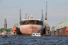 Schiffsreparatur im Schwimmdock an de Elbe - Fahrgastschiff mit Touristen vor dem Dock der Steinwerder Werft Blohm + Voss.