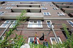 Hausfassade Klinkergebäude - Wildkraut im Vordergrund; ein Kinderrad ist am Geländer angeschlossen.