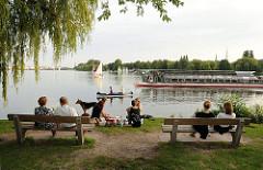 Die Hamburger geniessen den Abend im Alstergrün - sie sitzen auf Parkbanken oder im Gras. Ein solarbetriebenes Alsterschiff überholt ein Kanu auf der Aussenalster.