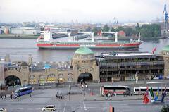 St. Pauli Landungsbrücken, einige Reisebusse stehen auf den Parkplätzen - ein Frachtschiff fährt elbabwärts.