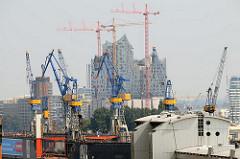 Blick vom Hamburger Stadtteil Altona Altstadt zur entstehenden Elphilharmonie in der Hafencity - im Vordergrund Kräne auf der Werft Blohm +  Voss.