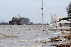 Sturmflutwarnung in Hamburg - Hochwasser an der Elbe - der Strand bei der Strandperle ist überspült - im Hintergrund verlässt ein Containerschiff den Hamburger Hafen.
