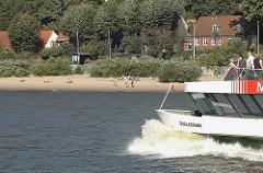 Elbstrand und Häuser von Hamburg Oevelgoenne, Stadtteil Othmarschen - die Hafenfähre Övelgönne fährt mit hoher Bugwelle auf der Elbe.