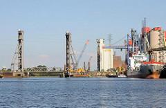 Blick über den Reiherstieghafen - rechts die Kaliumschlagsanlage; ein Frachtschiff hat am Kai festgemachte; in der Bildmitte die Rethehubbrücke, dahinter der Reiherstieg.