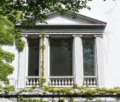 Mit Efeu bewachsene Hausfassade in der Palmaille - Fenster mit klassizistischen Verzierungen.
