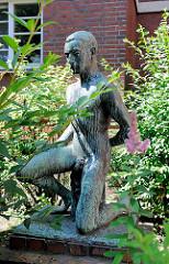 Bronzeskulptur knieender Jüngling im Vorgarten eines Wohnhause in Hamburg Barmbek Nord.