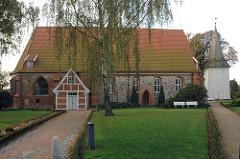 Seitenansicht der Kirche in Hamburg Neuengamme - St. Johanniskirche - mittelalterlicher Backsteinbau mit Feldsteinen verkleidet.