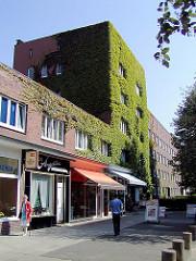 Mit wildem Wein bewachsenes Wohngebäude im Hanssensweg in der Jarrestadt - Geschäfte mit Markisen (ca. 2005)