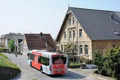 Hauptstrasse am Este-Deich - ein Bus der Hamburger öffentlichen Verkehrsmittel fährt durch HH-Cranz. Historische Häuser an der Strasse.