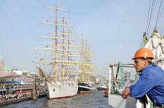 Ein Grosssegler legt nach der Einlaufparade an den St. Pauli Landungsbrücken an - weitere Segelschiffe haben schon an dem Anleger fest gemacht.