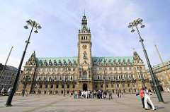 Frontansicht des Rathausgebäude in Hamburg - auf dem Rathausplatz steht eine Gruppe Touristen.