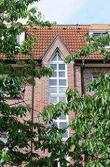 Fassade eines Neubaus in Hamburg Langenbek - Kirschbäume mit Früchten am Strassenrand.