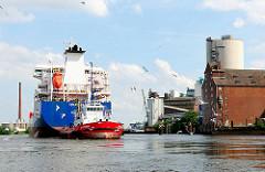 Tankschiff mit Schlepper im Reiherstiegkanal - rechts am Ufer Speichergebäude. Fotografien aus Hamburg Wilhelmsburg.