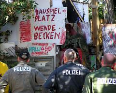 Polizisten stehen vor dem Tor des Bauwagenplatz Wendebecken kurz vor der Räumung. (2004)