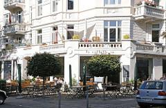 Hamburg Hoheluft Ost Strassencafe im Abendrothsweg. Stühle + Tische auf dem Fussweg.