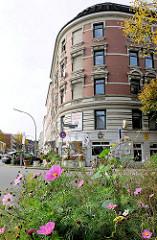 Gründerzeit-Wohngebäude in Hamburg Barmbek Süd - blühende Blumen am Strassenrand.