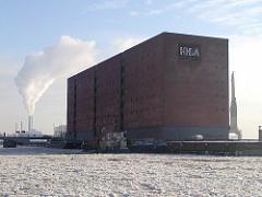 Kaispeicher A mit Logo der HHLA an der Fassade des Lagergebäudes. Die Einfahrt zum Grasbrookhafen und Elbe ist dicht mit Eis bedeckt - im Hintergrund kommt aus den Schornsteinen des Kraftwerks weisser Rauch.