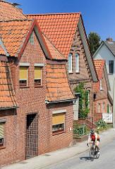 Klinker Wohnhäuser an der Deichstrasse - Fahrradfahrer mit Helm auf einem Rennrad.